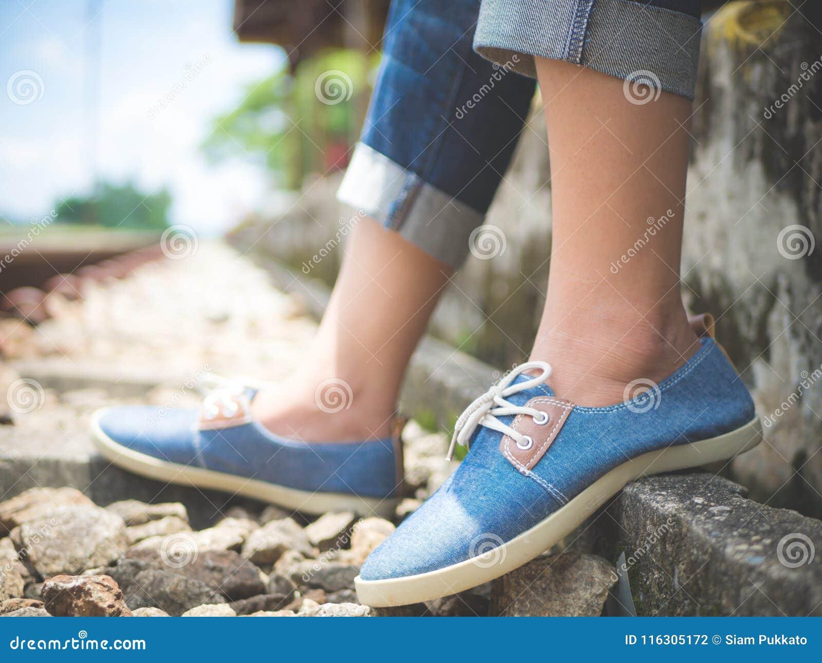 De voeten van de close-upvrouw in blauwe tennisschoenen die door de spoorweg zitten