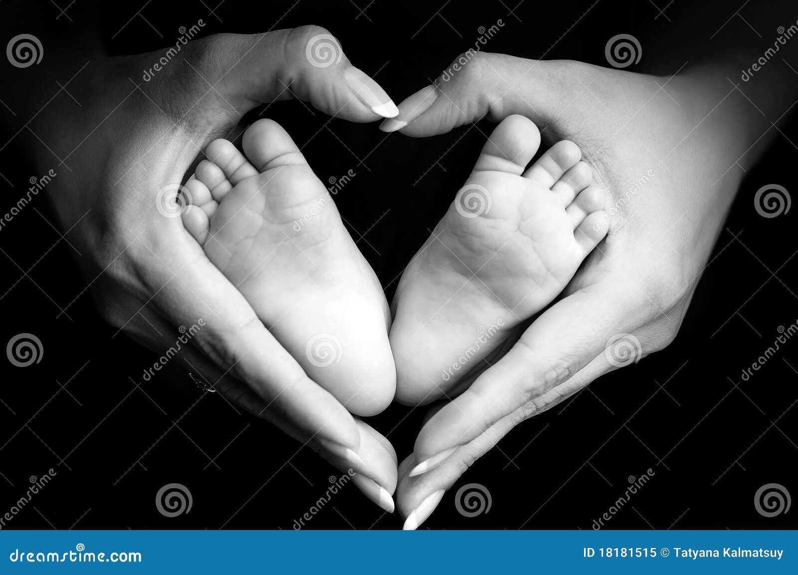 De voeten van de baby in de palmen van het mamma