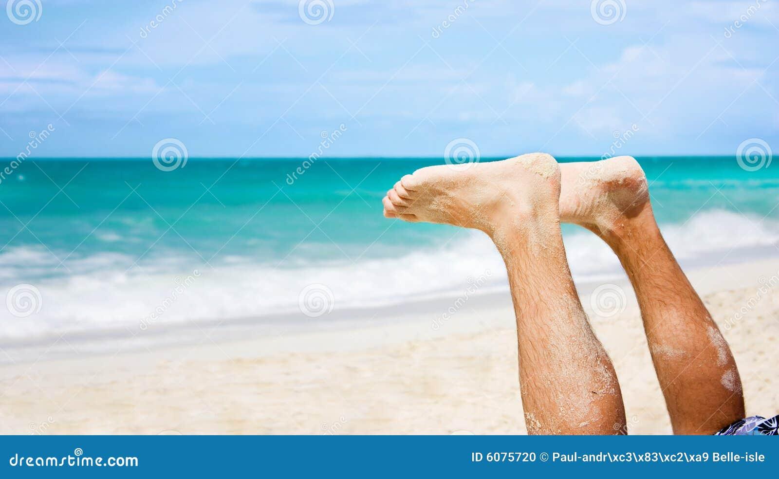 De voeten van de mens bij strand
