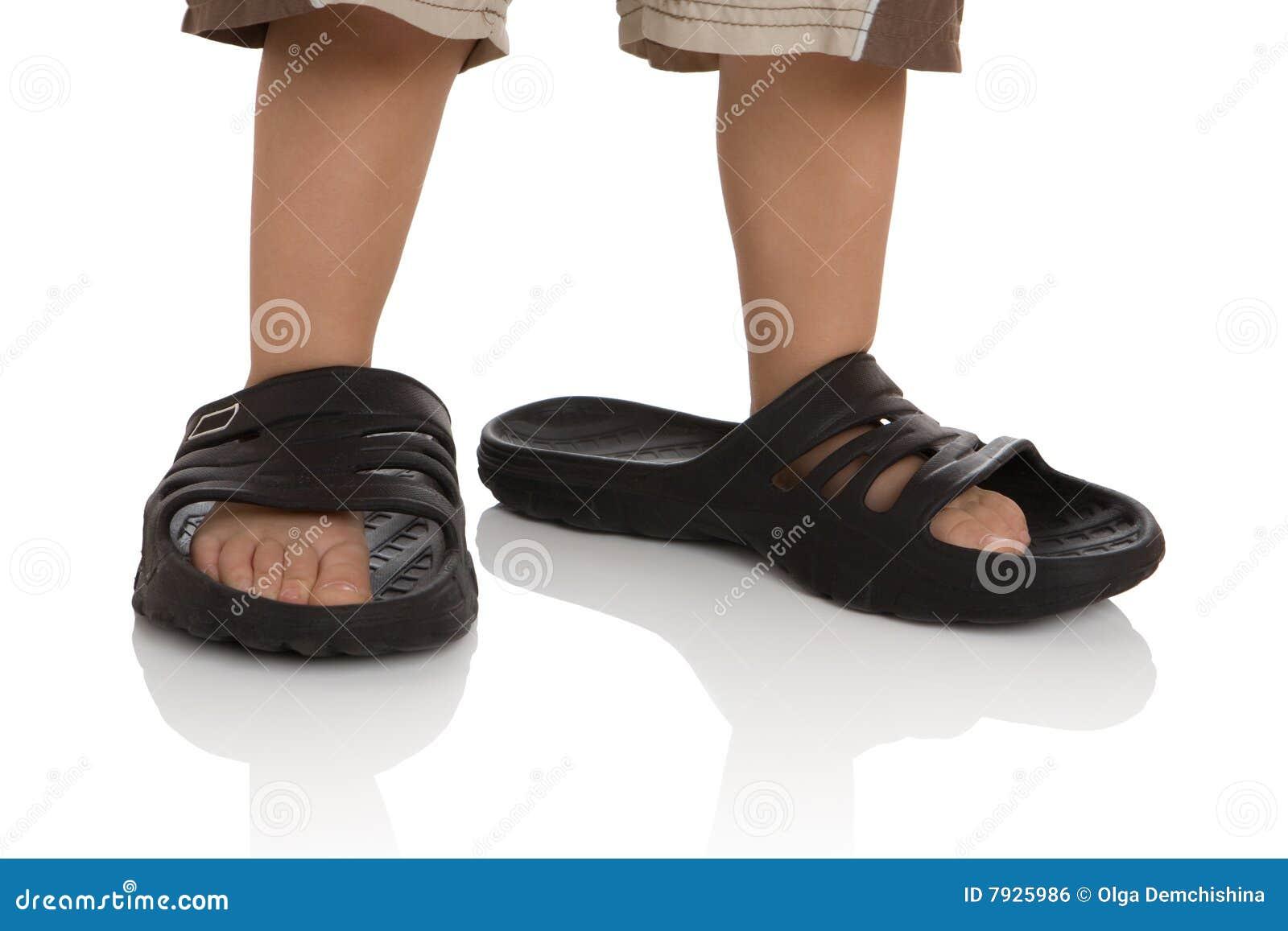 De voeten van het kind in grote pantoffels