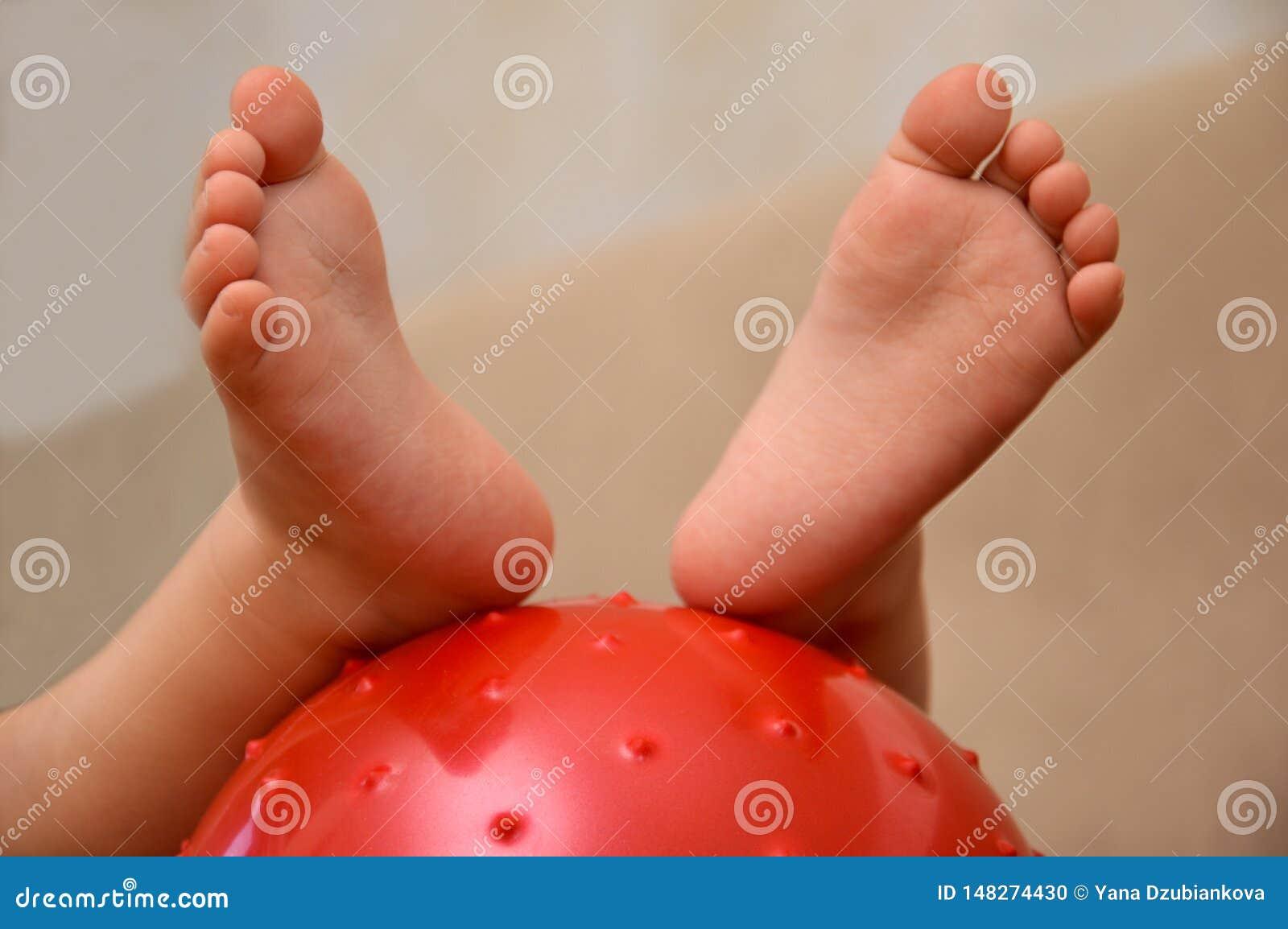 De voeten van kinderen op de bal Babyvoeten op de bal Kleine babyvoeten