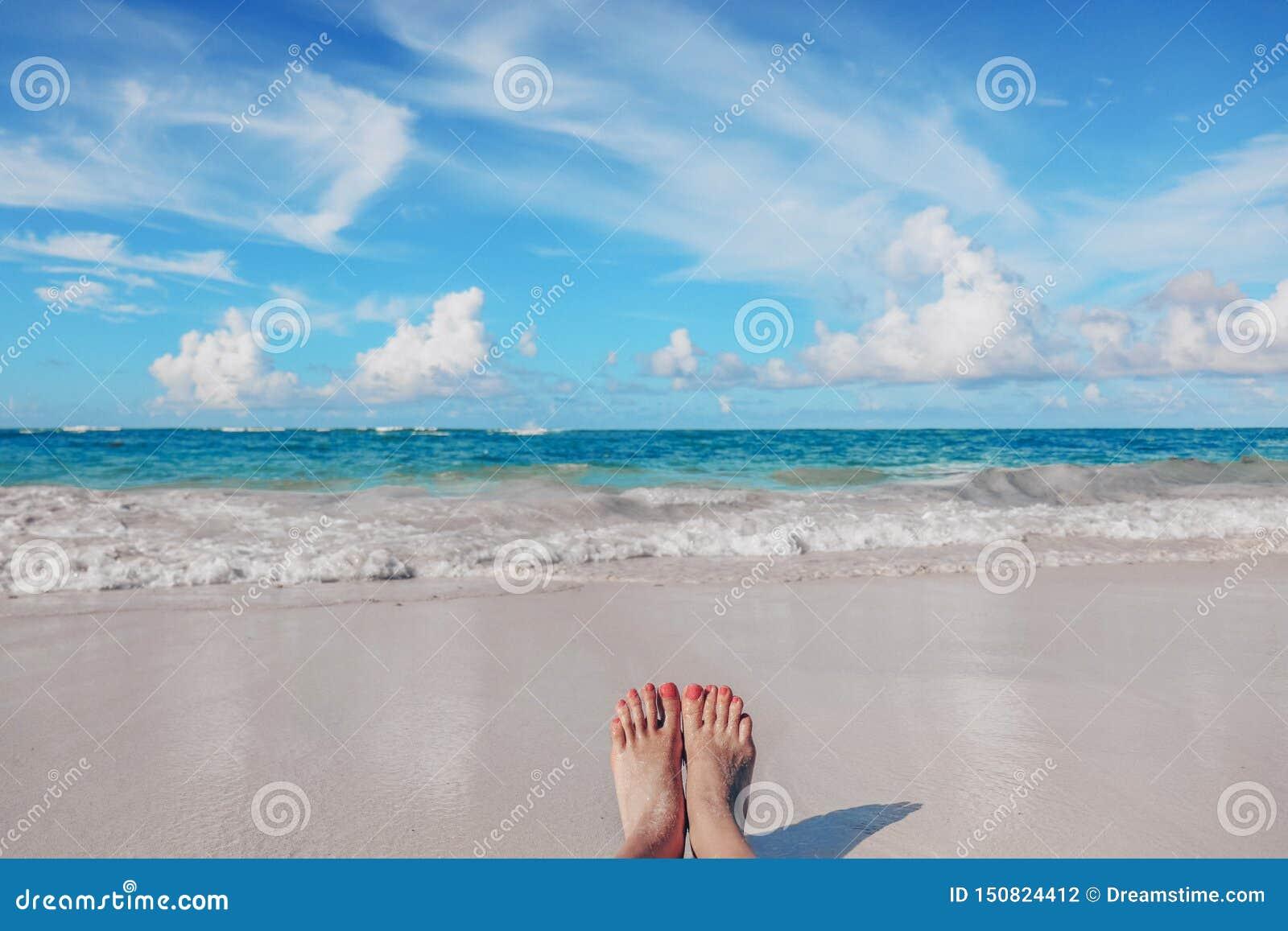 De voeten van de vrouw op het tropische Caraïbische strand Oceaan en blauwe hemel