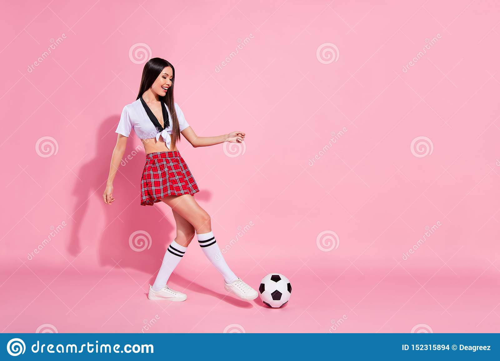 De volledige lengte zijfoto van koele van de de balvloer van het damevoetbal van de de spelerscore van de het doelslijtage rode k