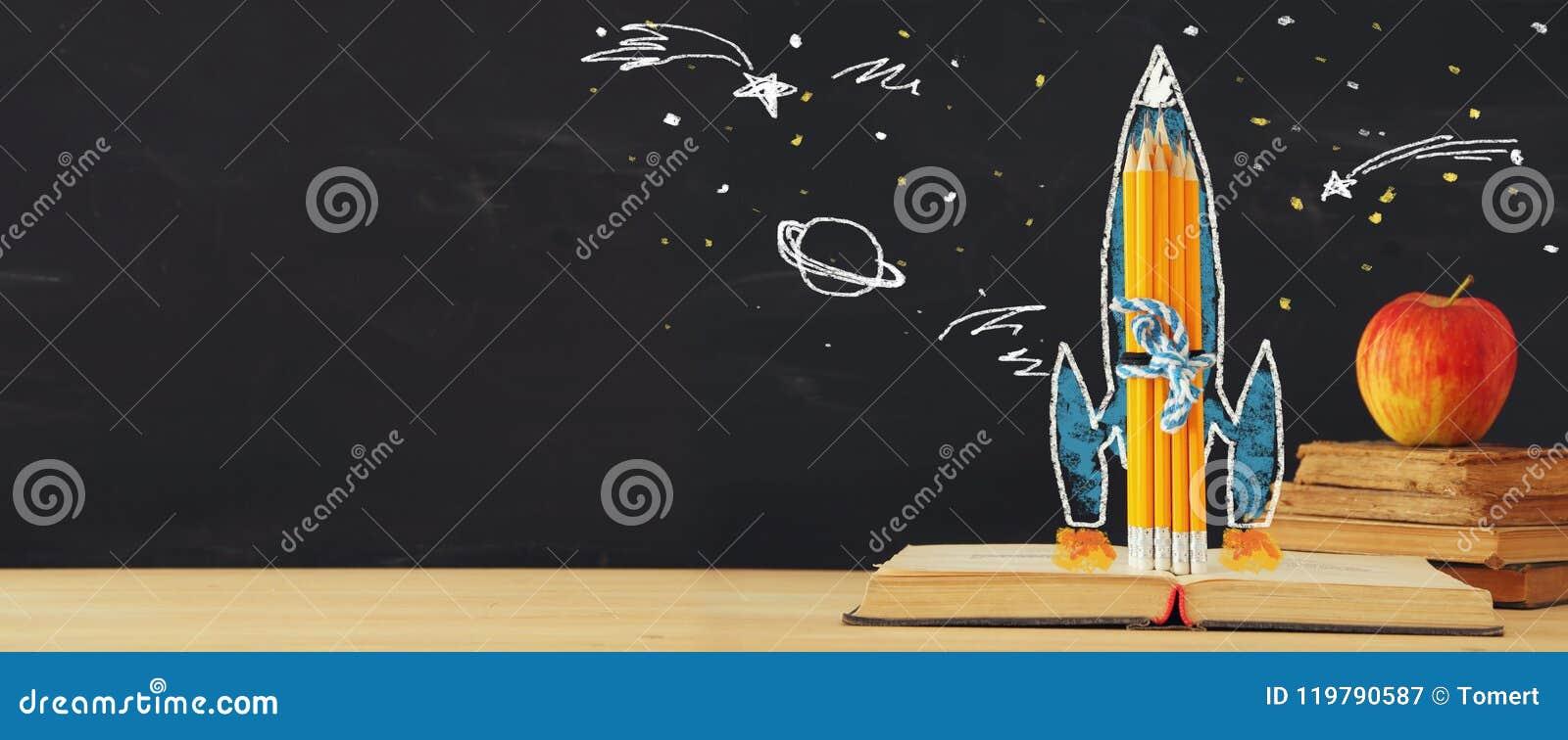 De volta à bandeira de escola suba rapidamente o esboço e os lápis sobre o livro aberto na frente do quadro-negro da sala de aula