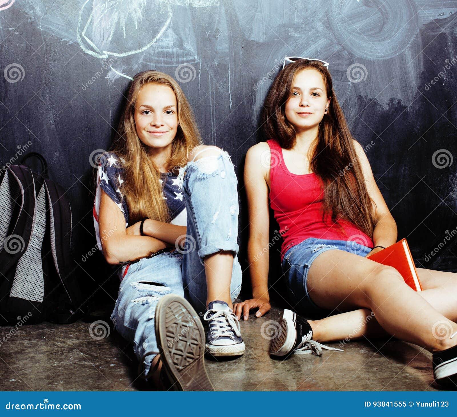 De volta à escola após férias de verão, duas meninas reais adolescentes na sala de aula com o quadro-negro pintado junto, estilo