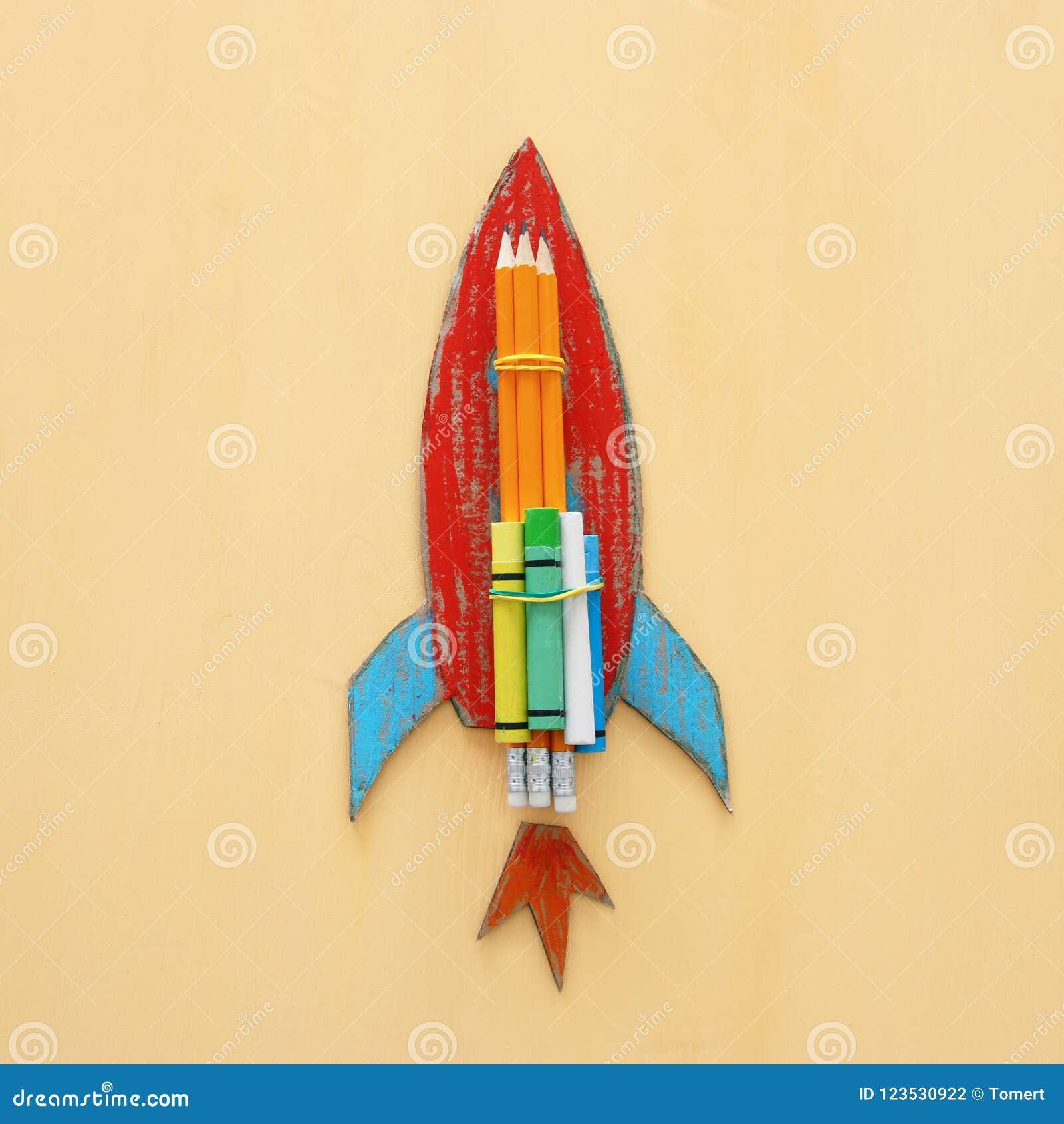 De volta ao conceito da escola corte do foguete do cartão do papel e pintado sobre o fundo amarelo de madeira