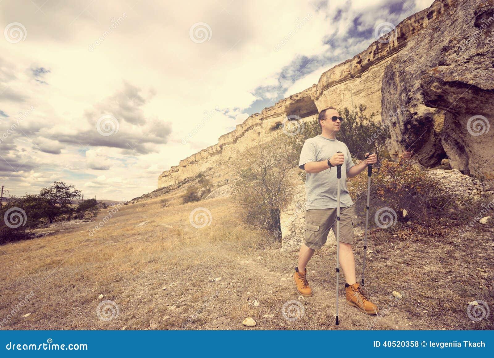 De volwassen mens wandelt met trekkingspolen