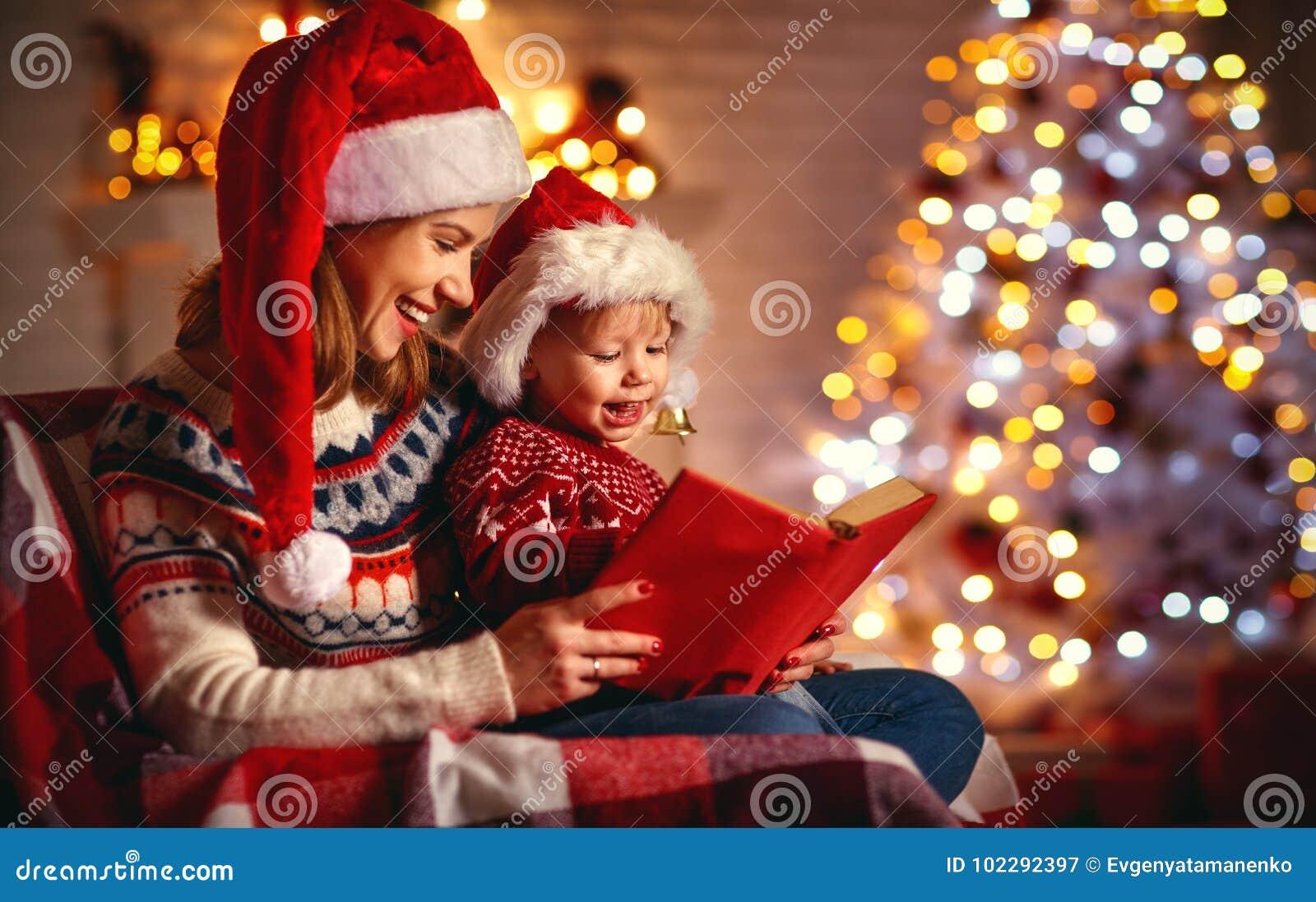 De vooravond van Kerstmis familiemoeder en baby die magisch boek thuis lezen