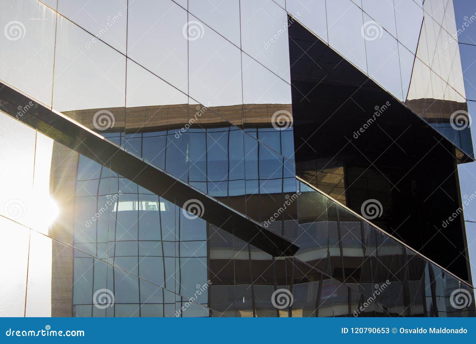 De voormuur van het glasvenster façade van een modern bureaugebouw met een bezinning van de een andere bureaubouw die zich in de