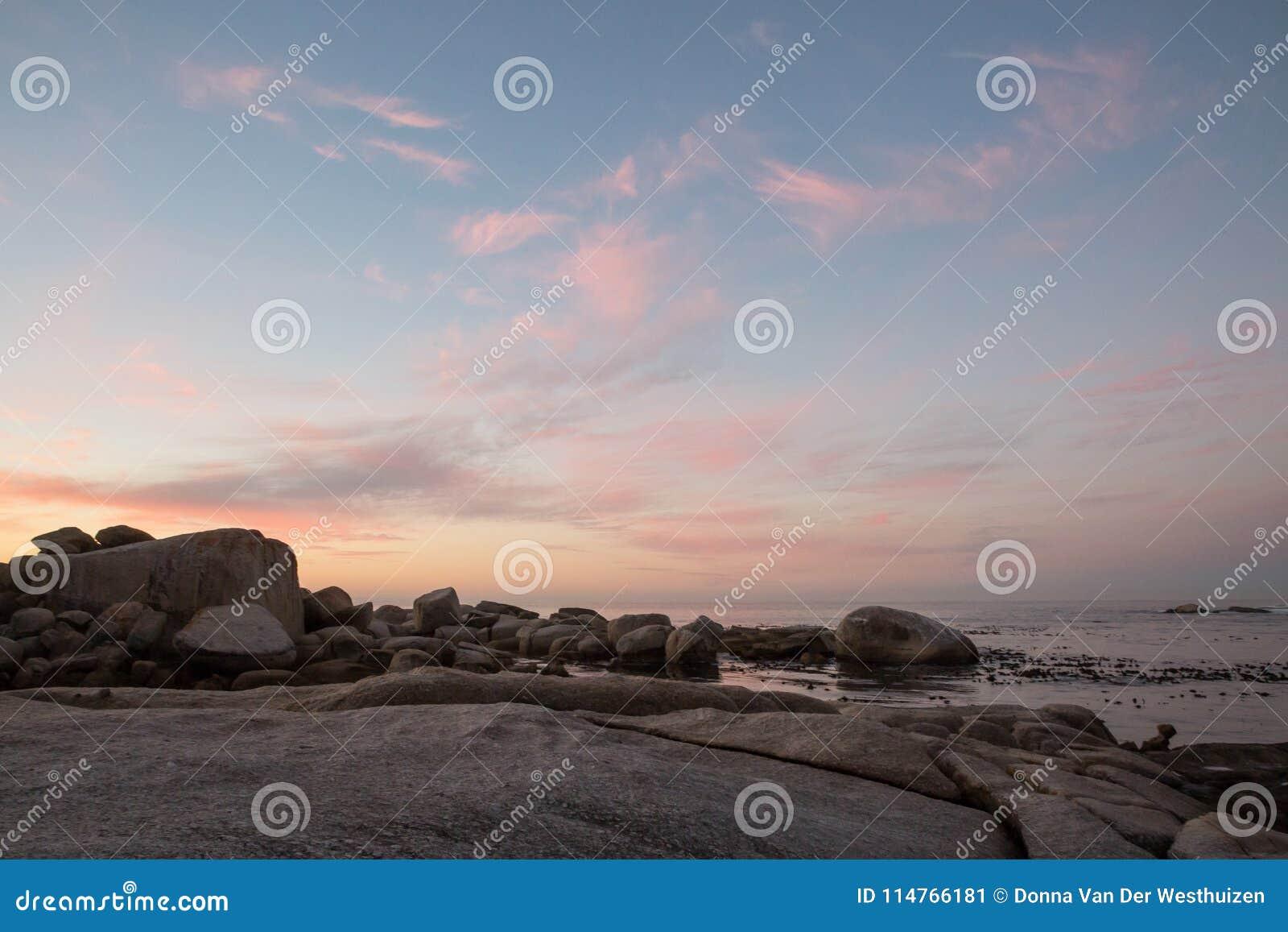 De vormingen van de kleurenwolk bij zonsondergang over het water