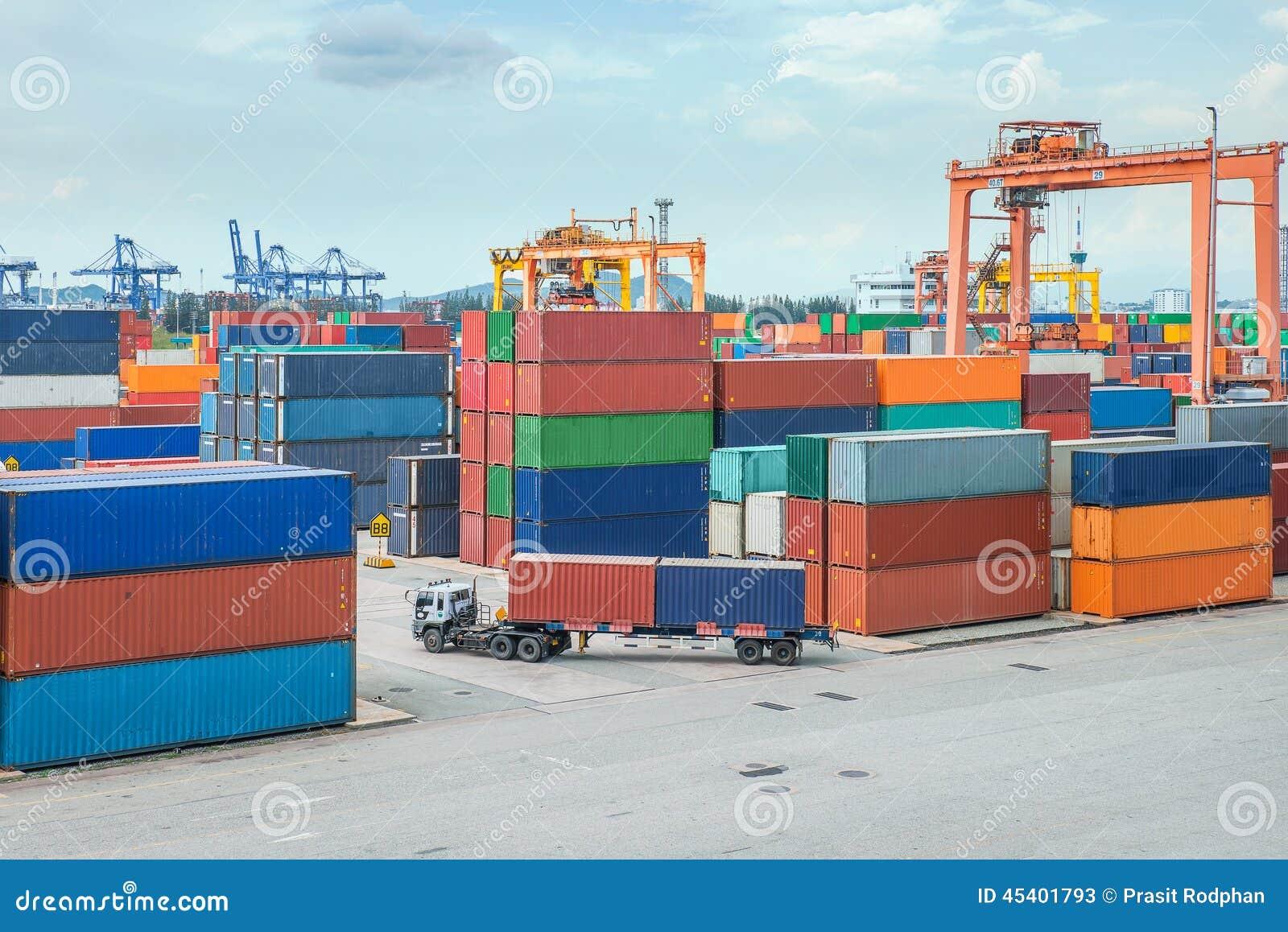 De vrachtwagen draagt container aan een pakhuis in dok