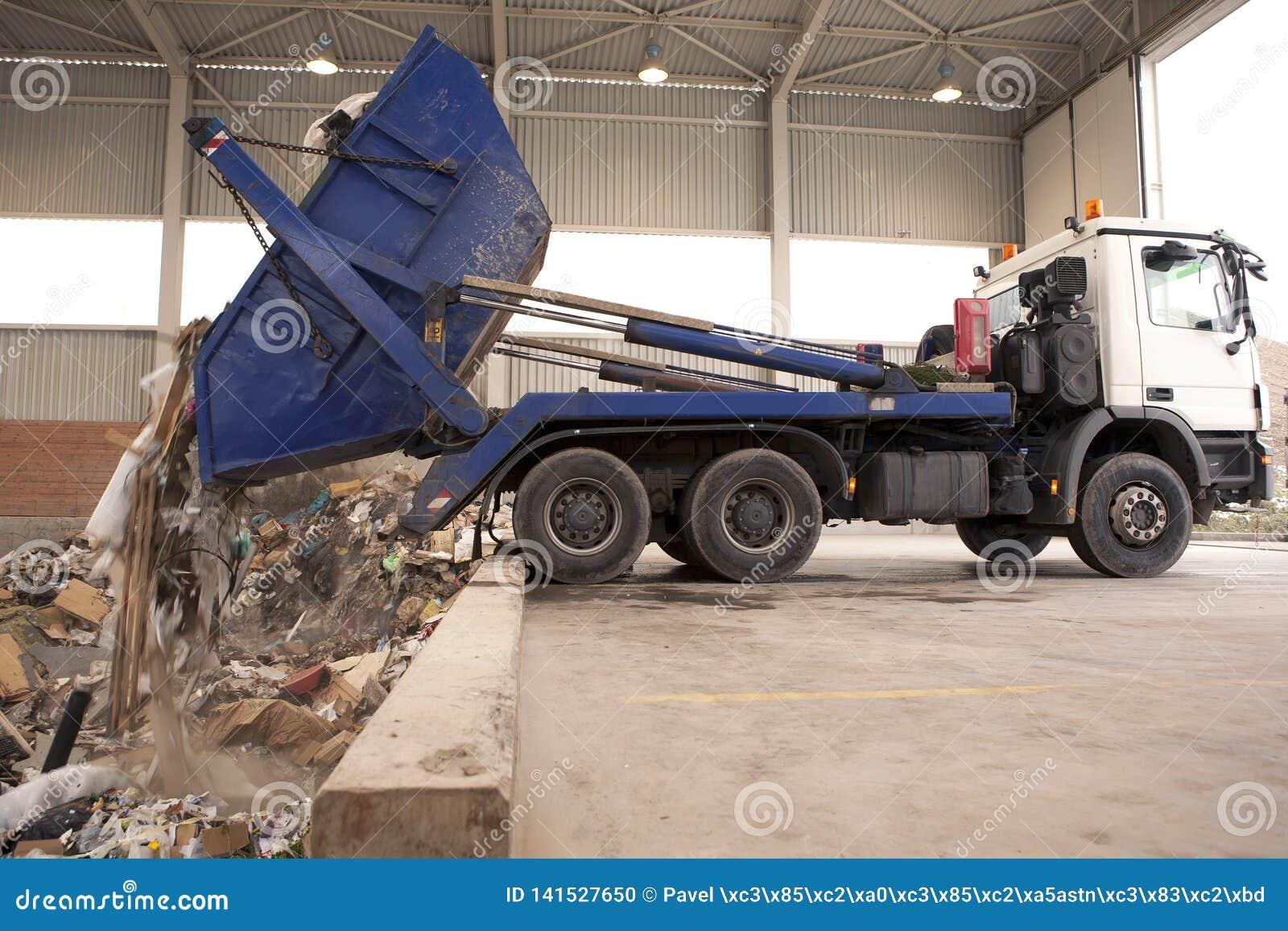 De vrachtwagen dumpt afval aan de verbrandingsoven, gat waar de grote greep het vuilnis neemt en zette het in brand Al afval word