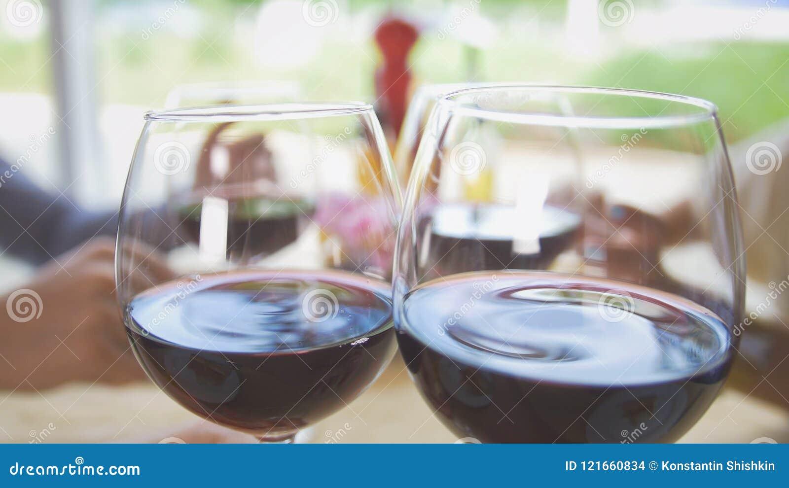 De vrienden communiceren in het restaurant, brengt de kelner hen wijn