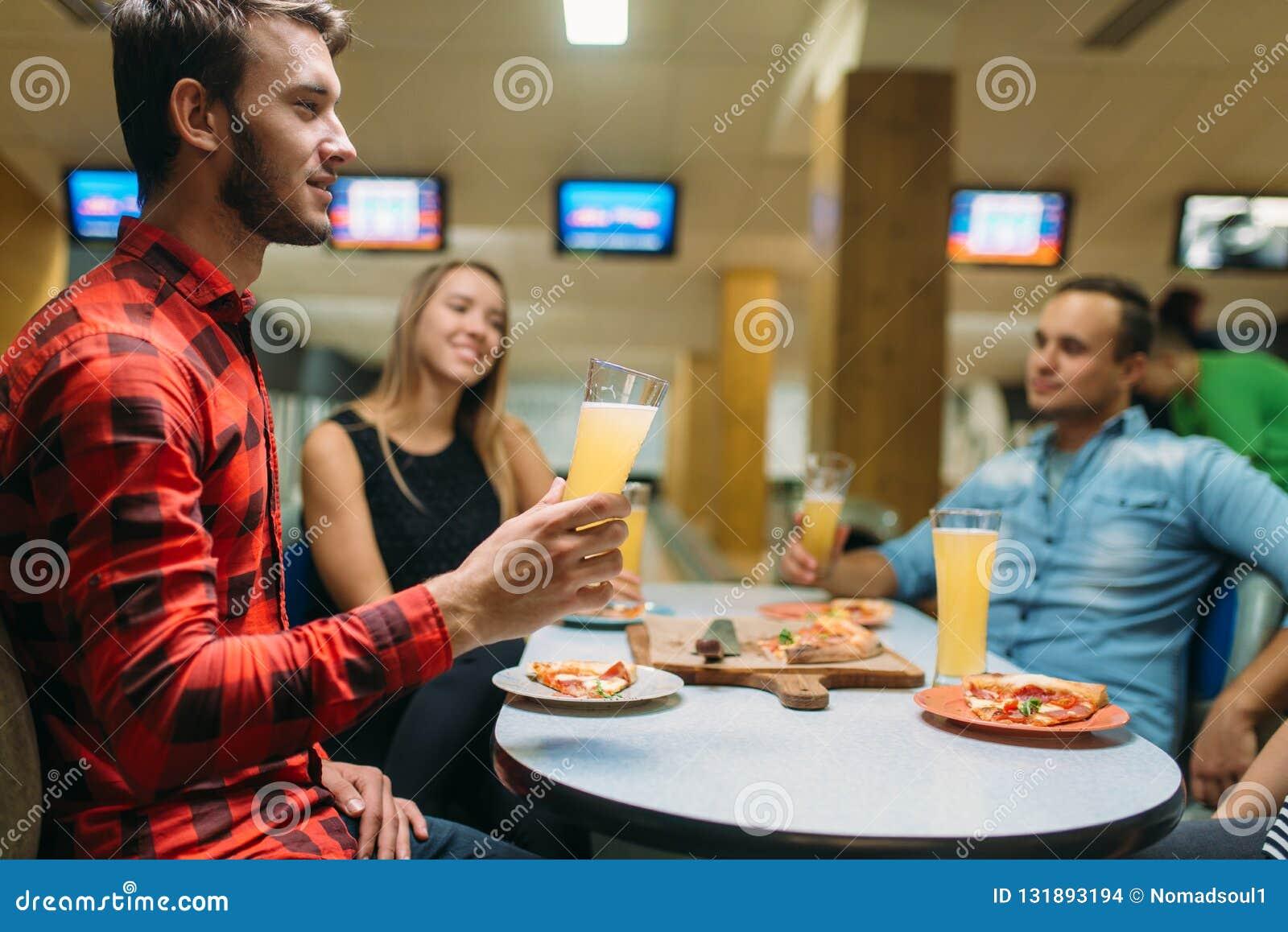 De vrienden drinkt en eet pizza in kegelenclub