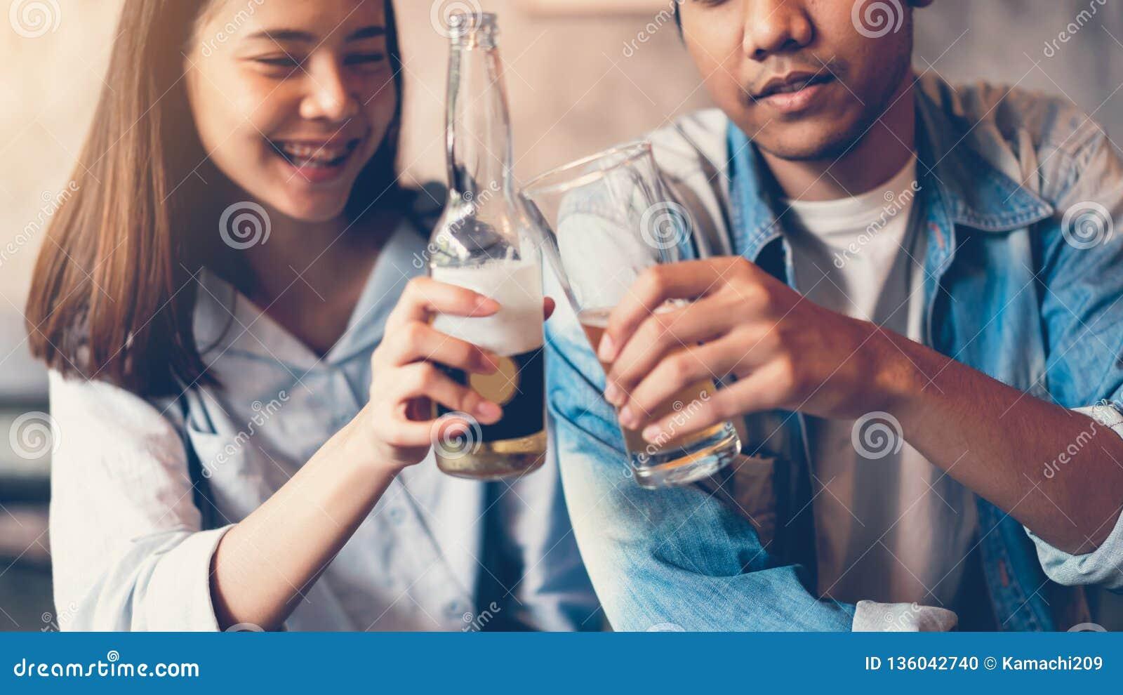 De vrienden glimlachen, gelukkige partying in de bar en sprekende en clinking fles met dranken