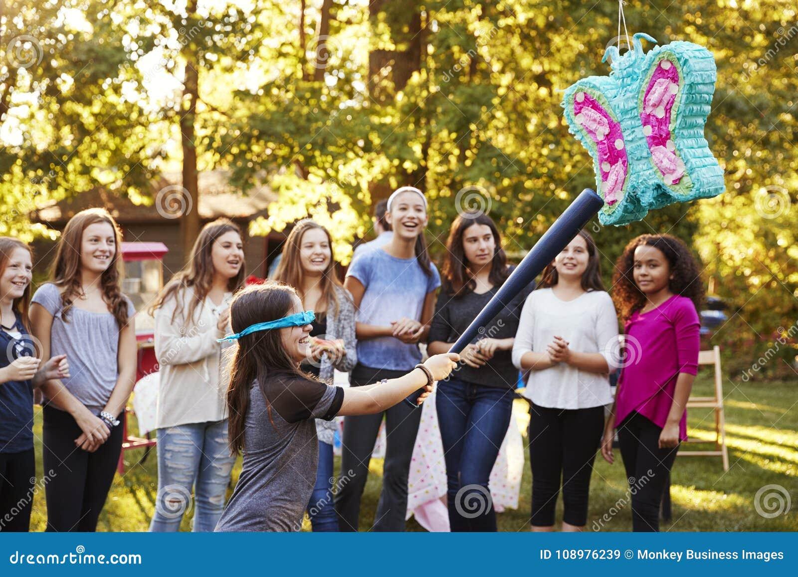 De vrienden letten op een jong meisje rakend een piï ¿ ½ ata op haar verjaardag