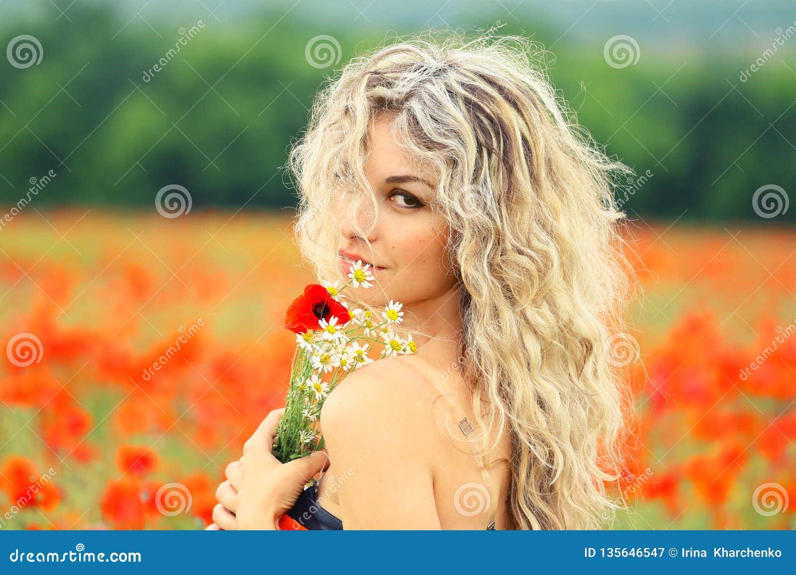 De vrij aantrekkelijke dame met blond krullend haar dat op haar gezicht, op een mooi rood papavergebied viel, draait aan de camer