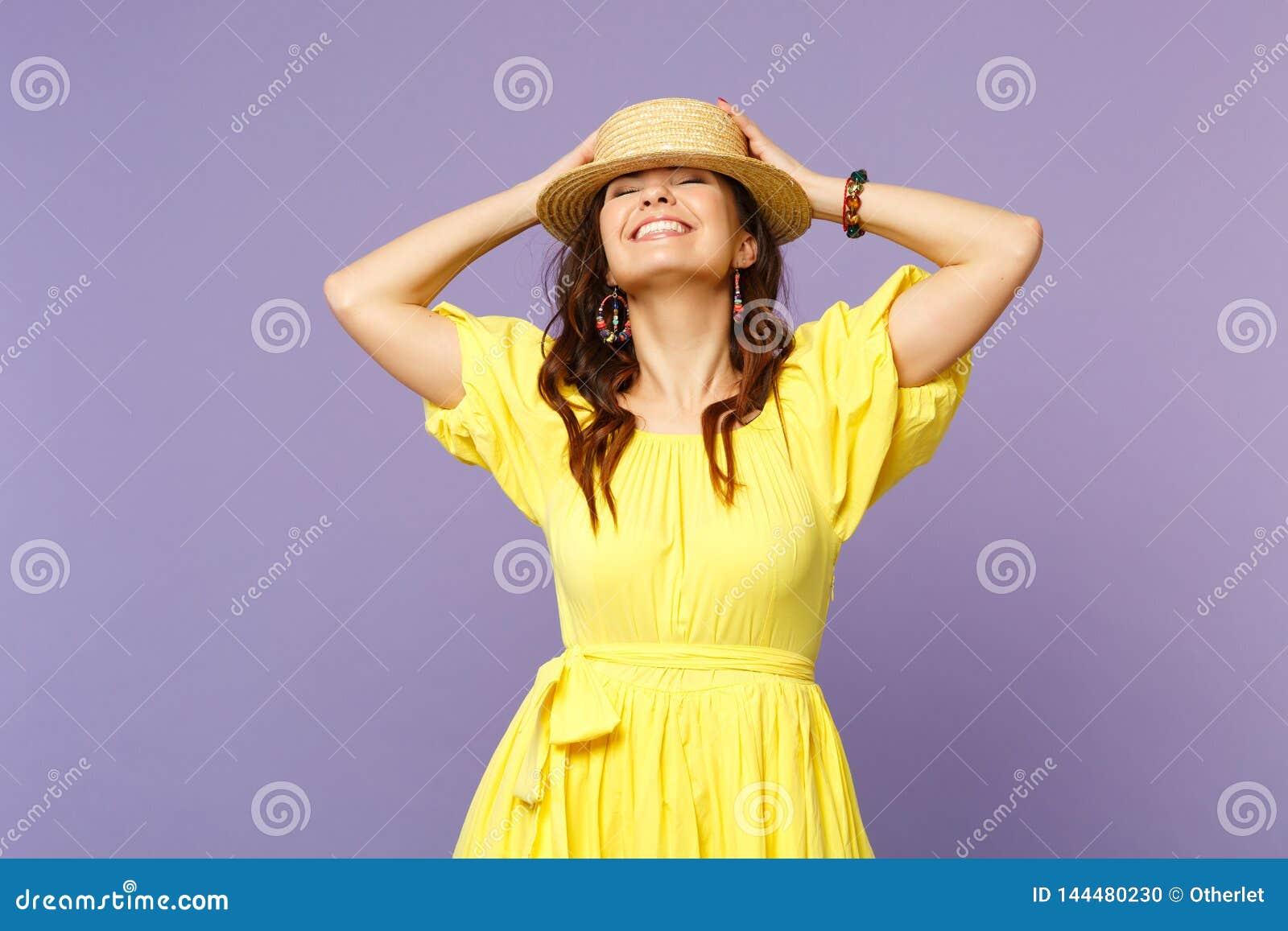 De vrij glimlachende jonge vrouw in gele kleding, de zomerhoed die ogen houden sloot, zettend handen op hoofd dat op pastelkleur