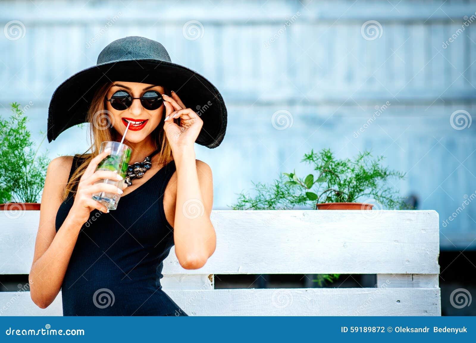 De vrij jonge koude van de meisjesdrank coctail openlucht in strandkoffie