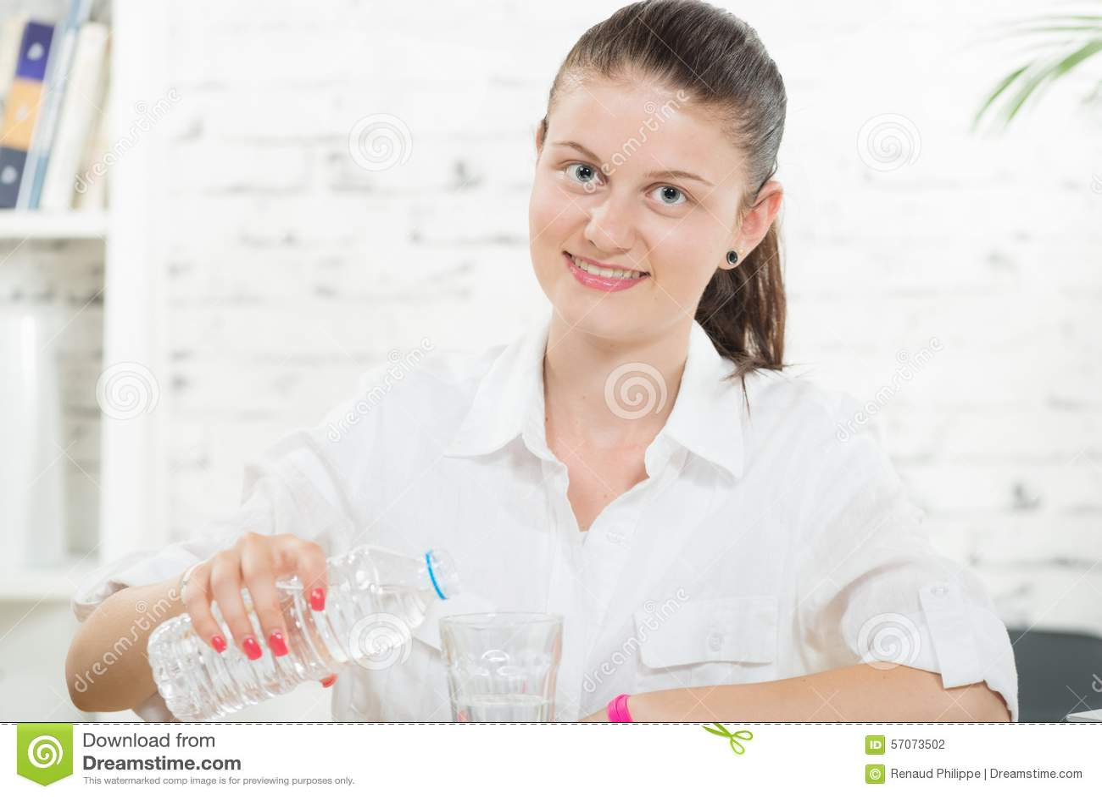 De vrij jonge vrouw giet glas water