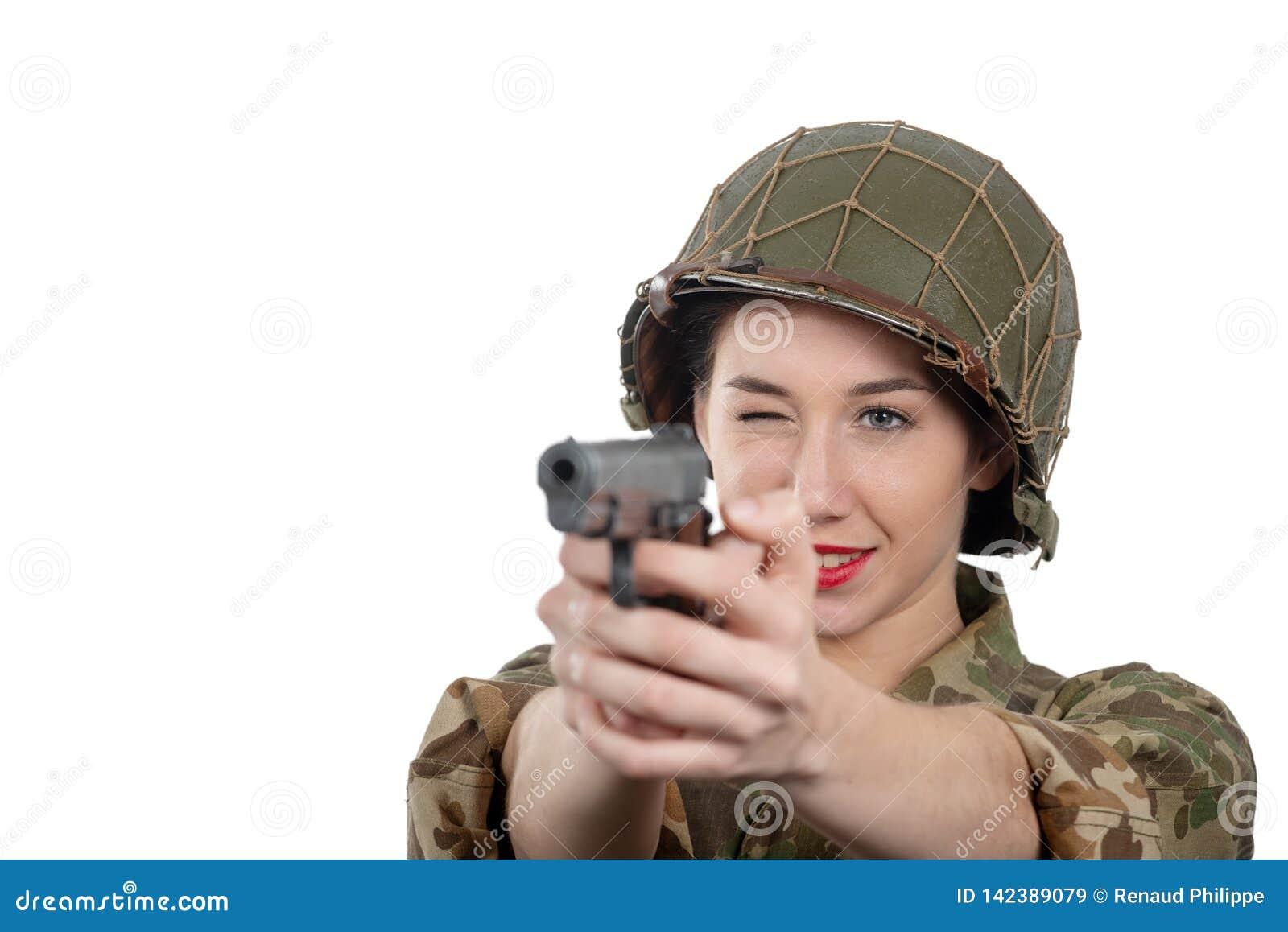De vrij jonge vrouw kleedde zich in Amerikaanse militaire eenvormig van ww2 met helm en pistool