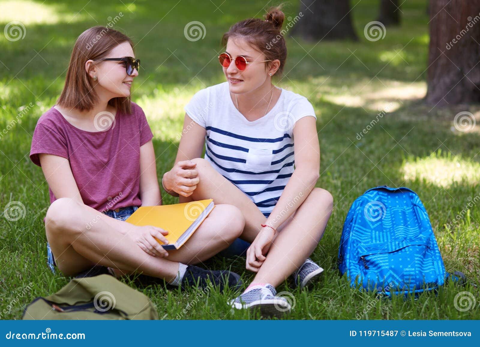 De vrij vrouwelijke kereltjes in vrijetijdskleding bekijkt vreugdevol elkaar, hebt rust na lezing voor definitief examen, zit op