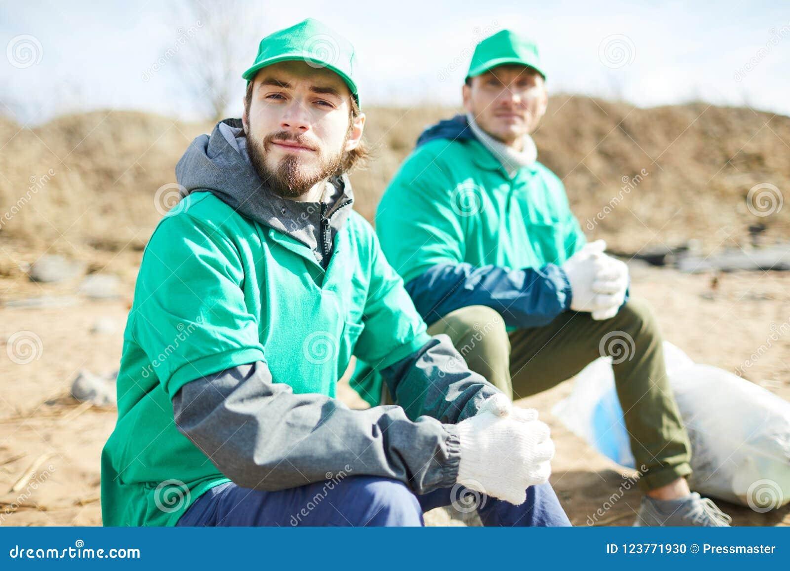 De vrijwilligers die bij vuilnis zitten doen in zakken