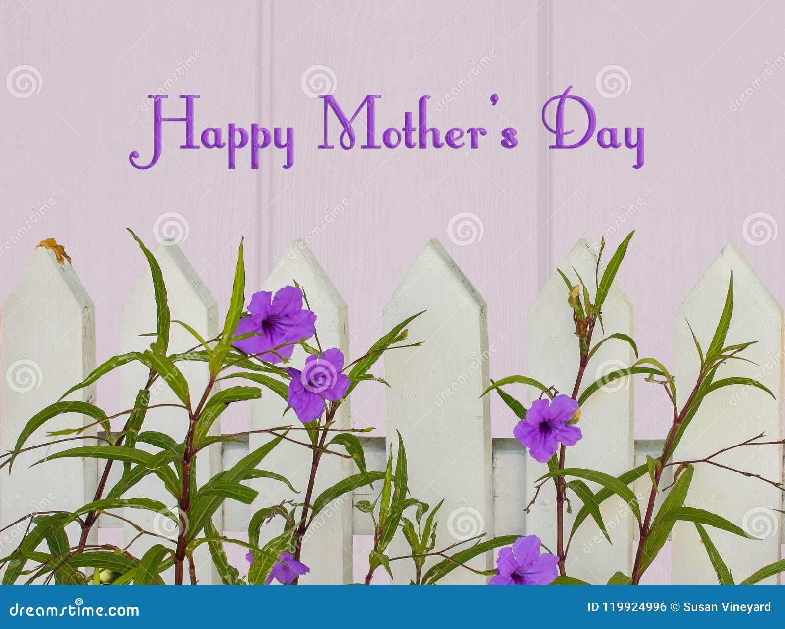 De vrolijke en gelukkige groet van de Moedersdag met piketomheining en purpere bloemen op lichtpaarse houten achtergrond met het
