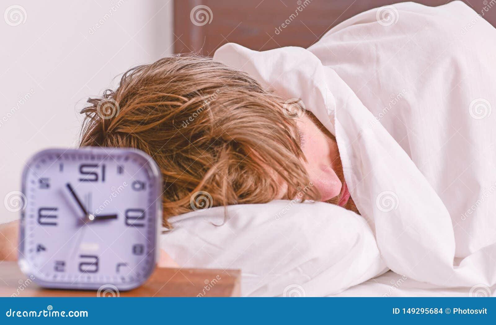 De vrolijke jonge mens is ontwaken na het slapen in de ochtend Mens het uitrekken zich in bed Ontspan in het bed