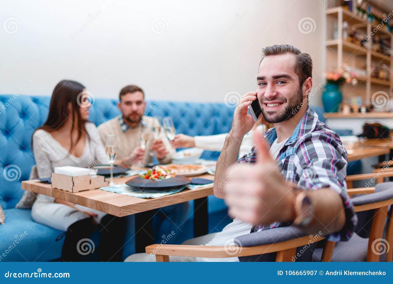 De vrolijke kerel spreekt op de telefoon en toont zijn duim, zittend in een koffie met vrienden