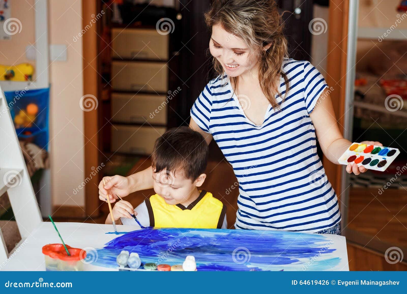 De vrolijke kinderjaren weinig jongen die met zijn moeder spelen trekken schilderen op de - Schilderen kind jongen ...
