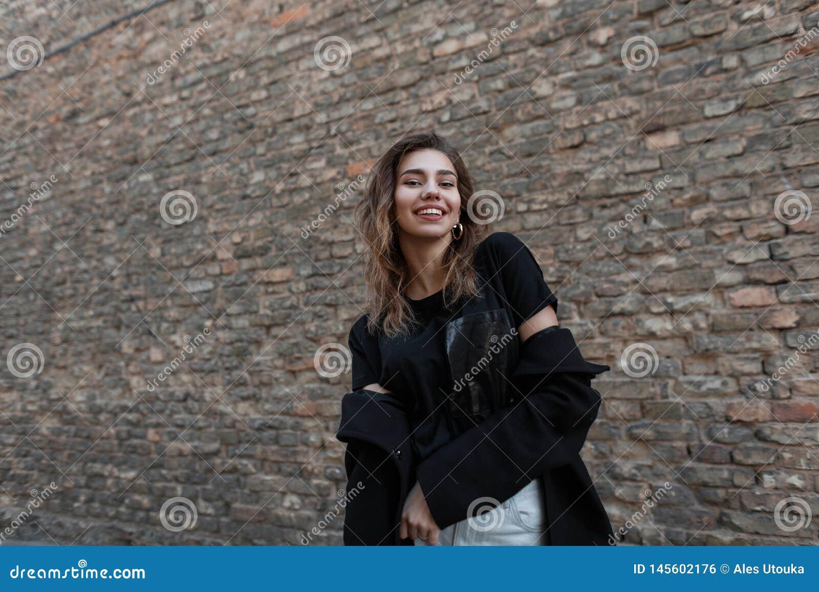 De vrolijke positieve jonge vrouw met een mooie glimlach in modieuze kleren bevindt zich in openlucht in de stad