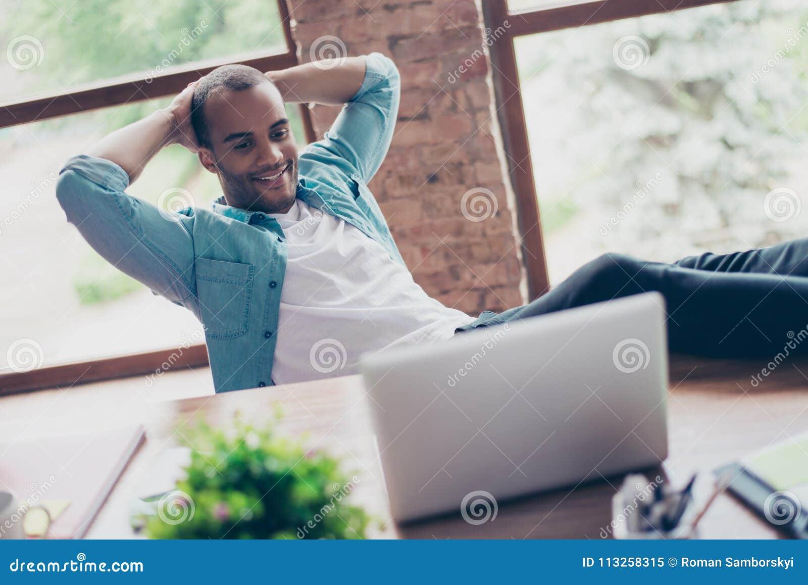 De vrolijke zwarte kerel let bij het zijn laptop scherm, op zijn het werkplaats, met wapens achter het hoofd, op het rusten, glim