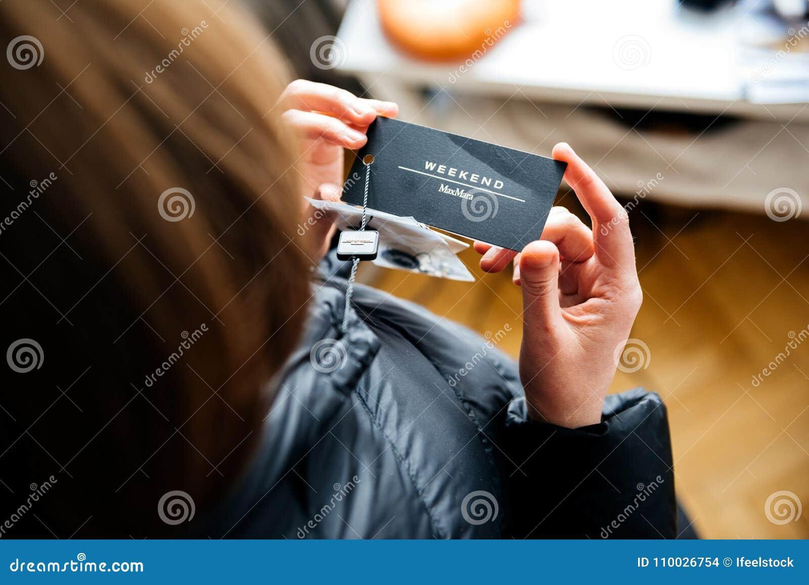 De vrouw die in Maximum mara onderaan jasje bekijken koopt nieuw klerenprijskaartje