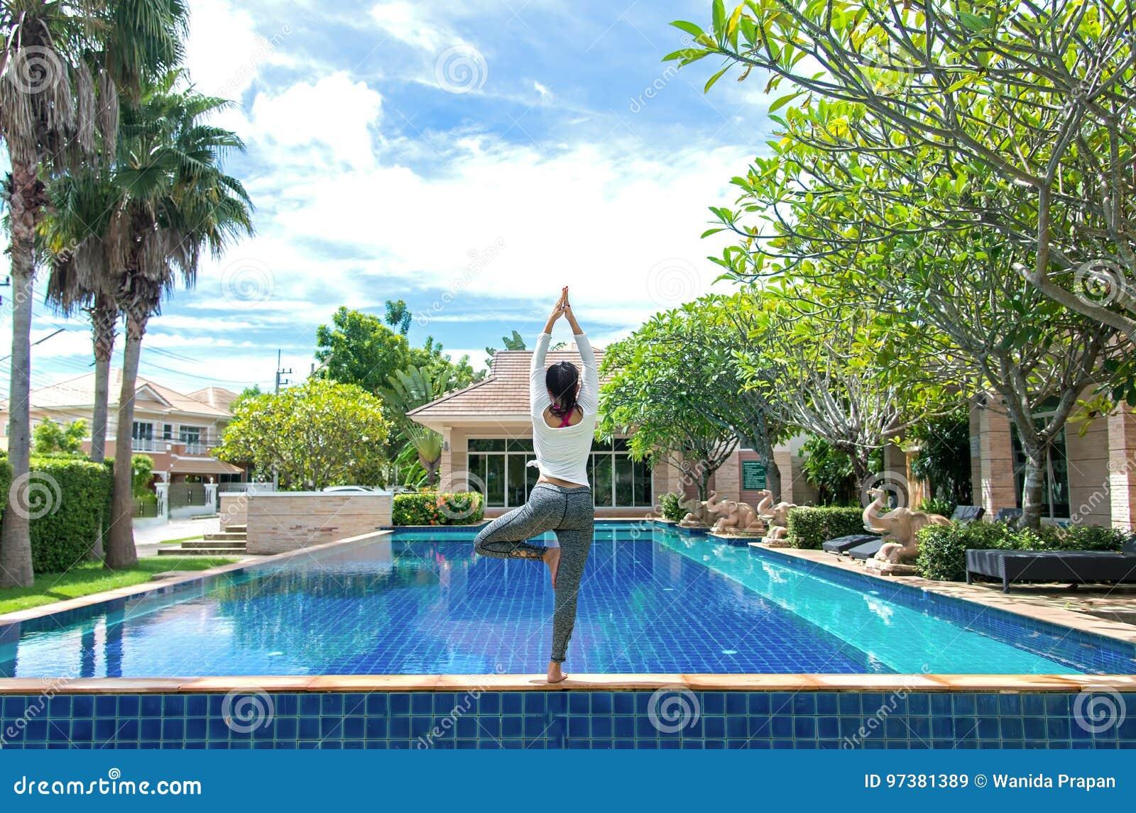 De vrouw die van Azië de oefening van de yogageschiktheid doen voor ontspant en gezond naast zwembadachtergrond
