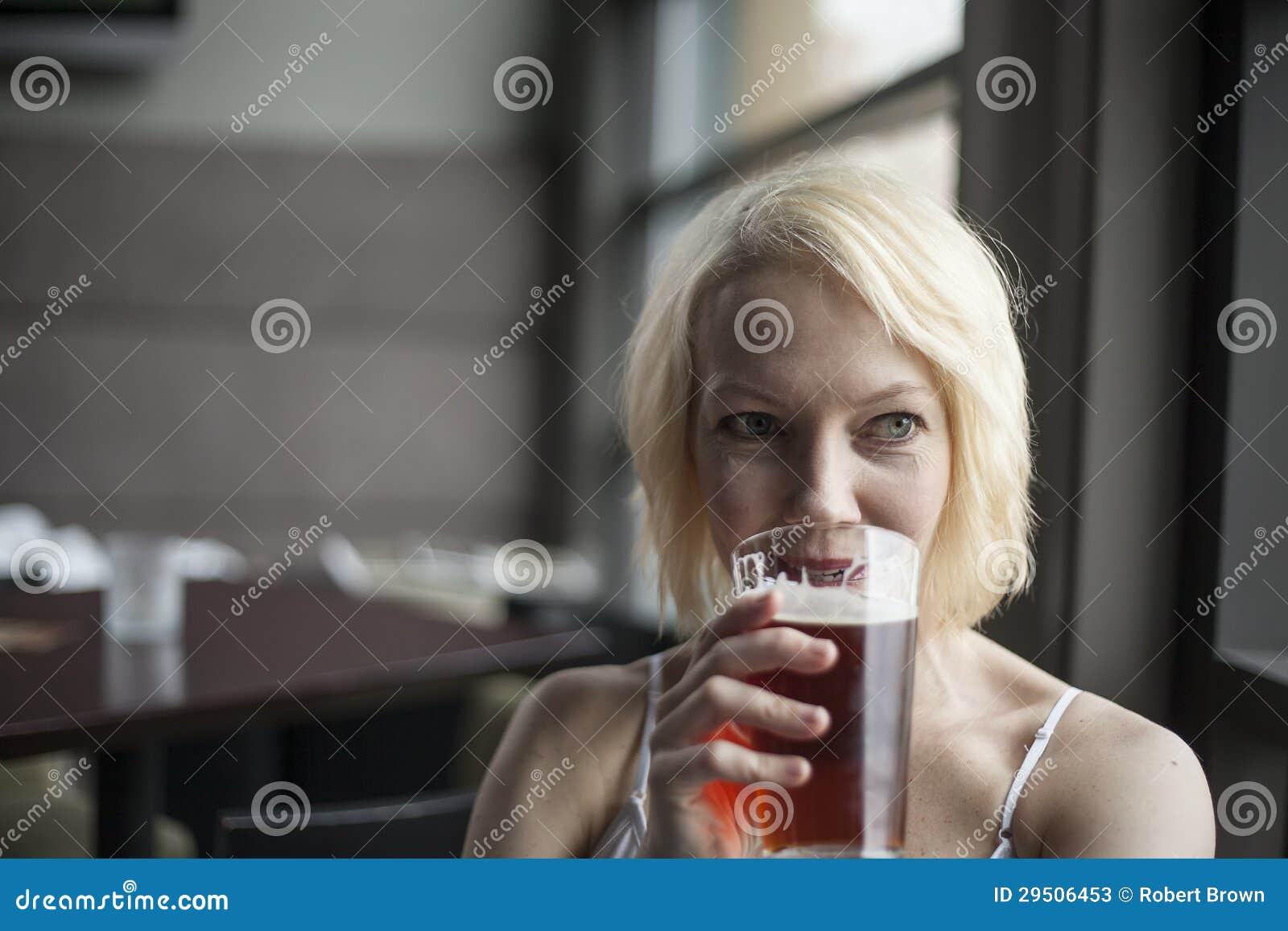 De Vrouw die van de blonde met Mooie Blauwe Ogen Glas Pale ale drinken