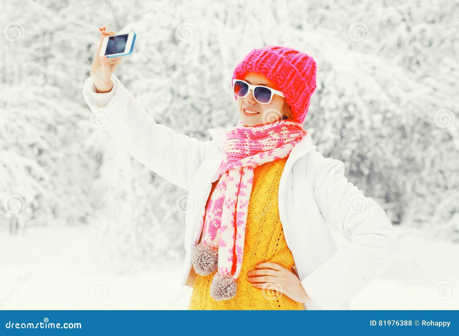 De vrouw die van de manierwinter beeld zelfportret op smartphone over sneeuwbomen nemen die een kleurrijke gebreide hoedensjaal d