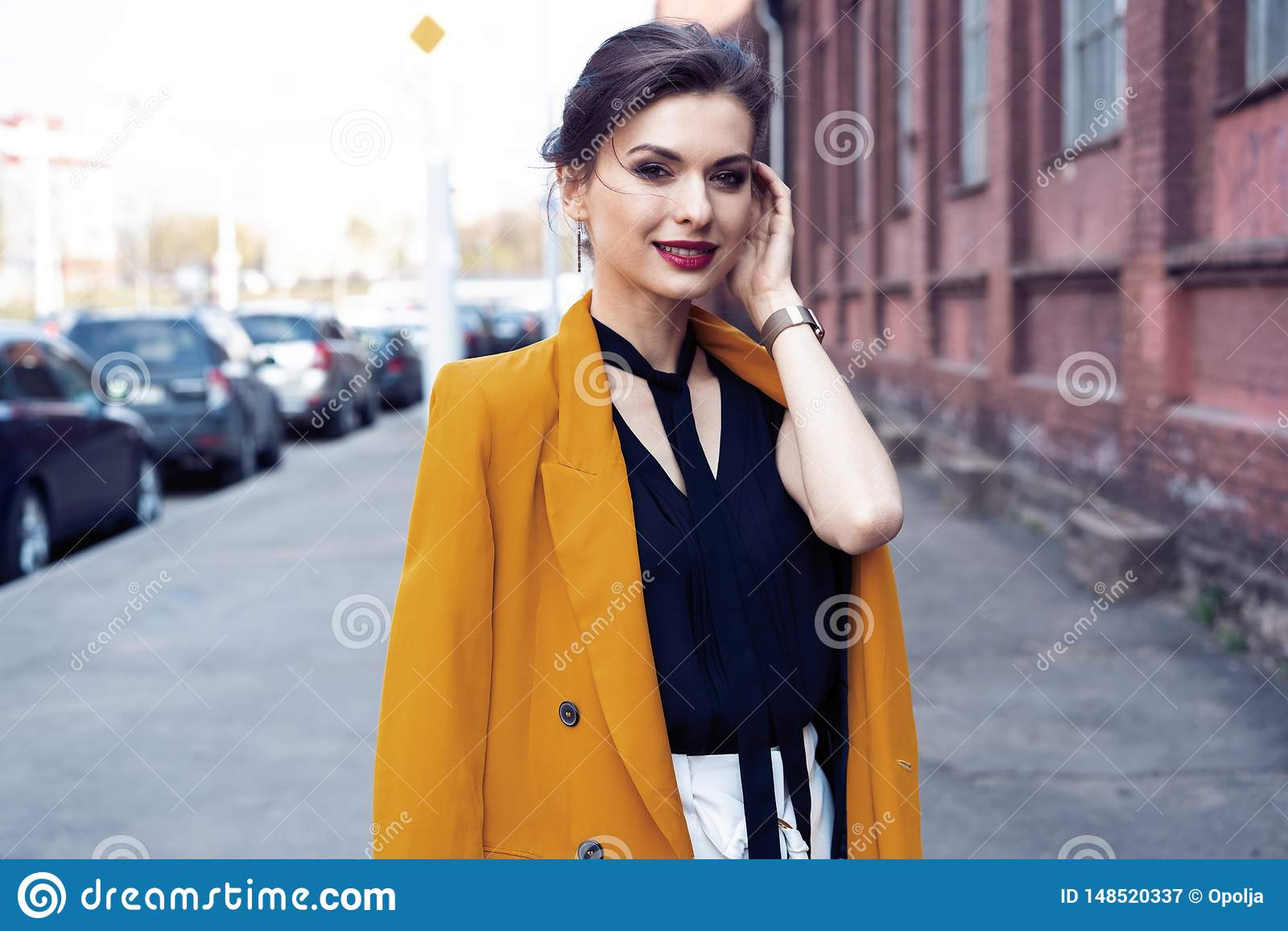 De vrouw die van de portretmanier op straat lopen Zij draagt geel jasje, glimlachend aan kant
