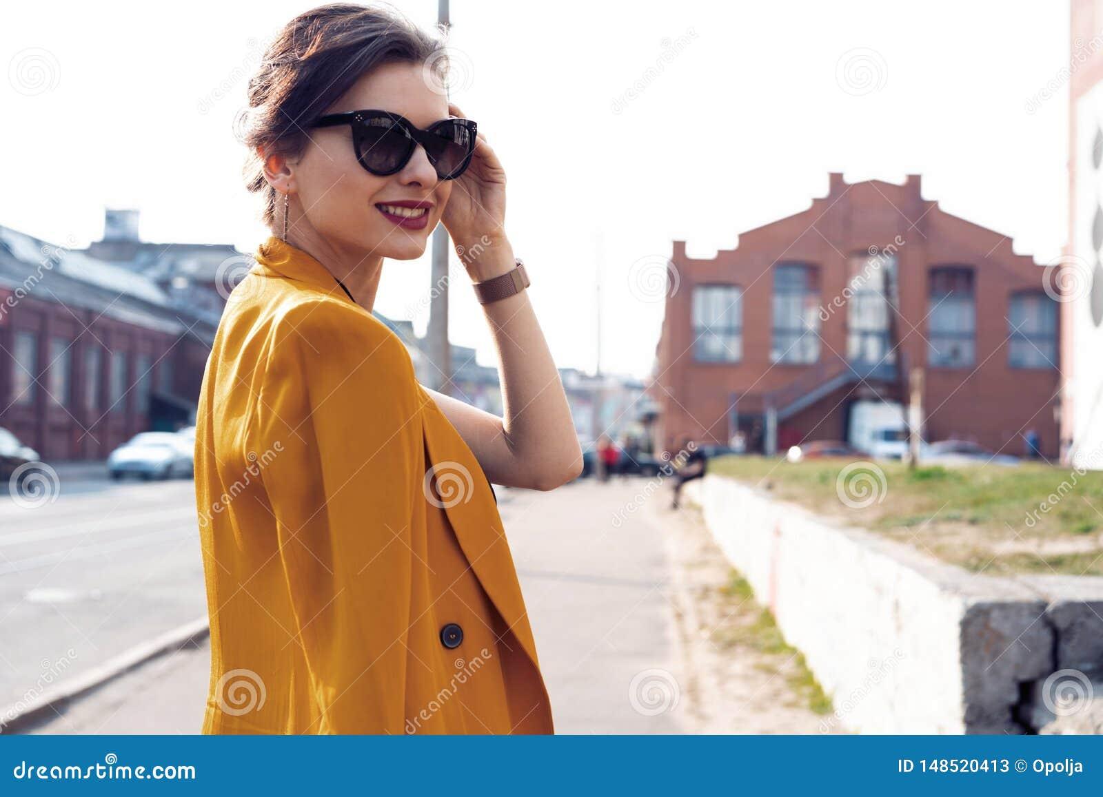 De vrouw die van de portretmanier in zonnebril op straat lopen Zij draagt geel jasje, glimlachend aan kant