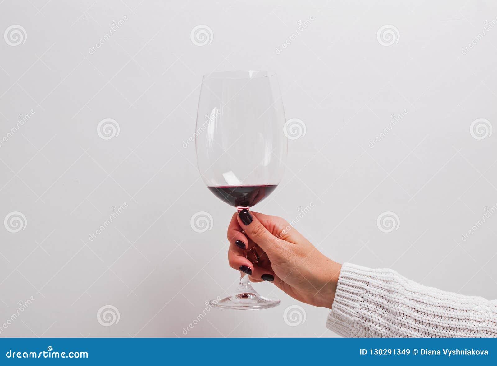 De vrouw dient een witte sweater in houdend een glas rode wijn