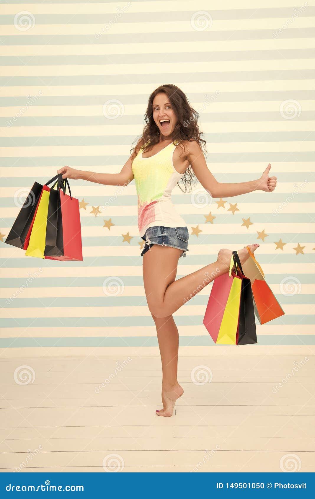 De vrouw draagt bos het winkelen zakken gestreepte achtergrond Tot slot gekocht favoriet merk De verkoop van de uiteindenwinkel T