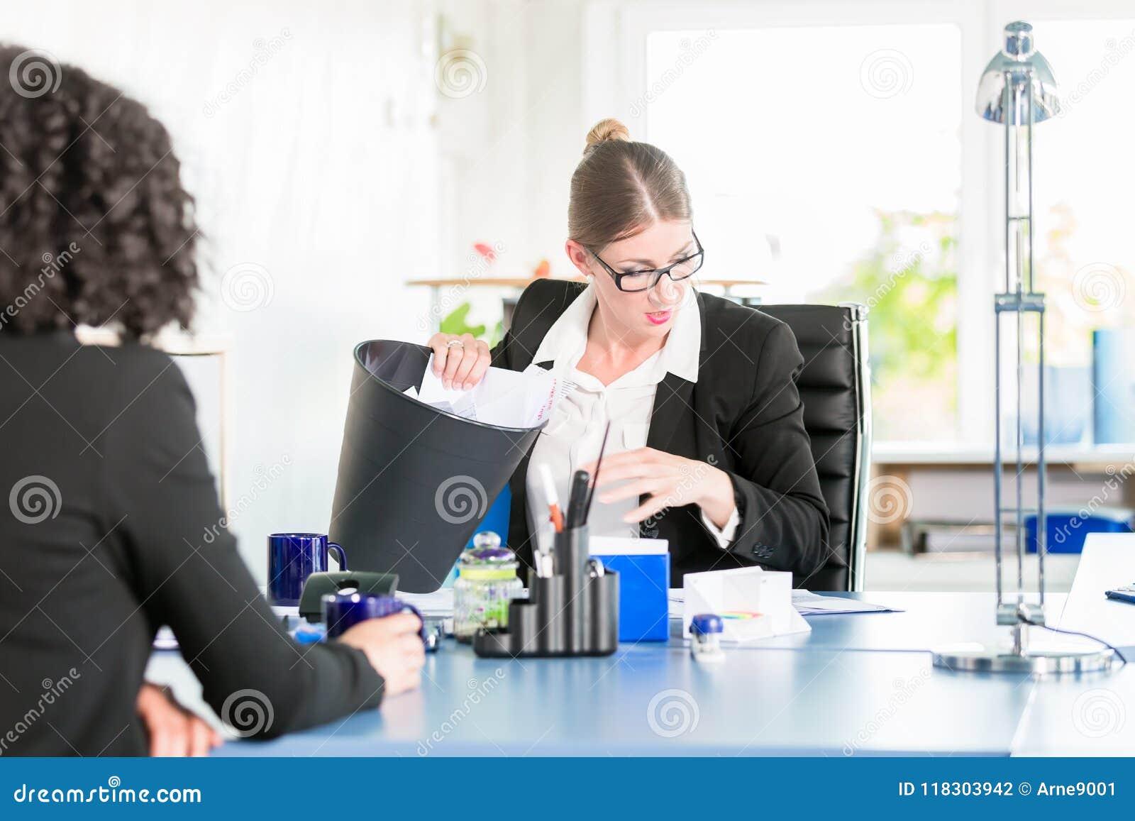 De vrouw in een bureau zoekt een verloren nota in de document bak