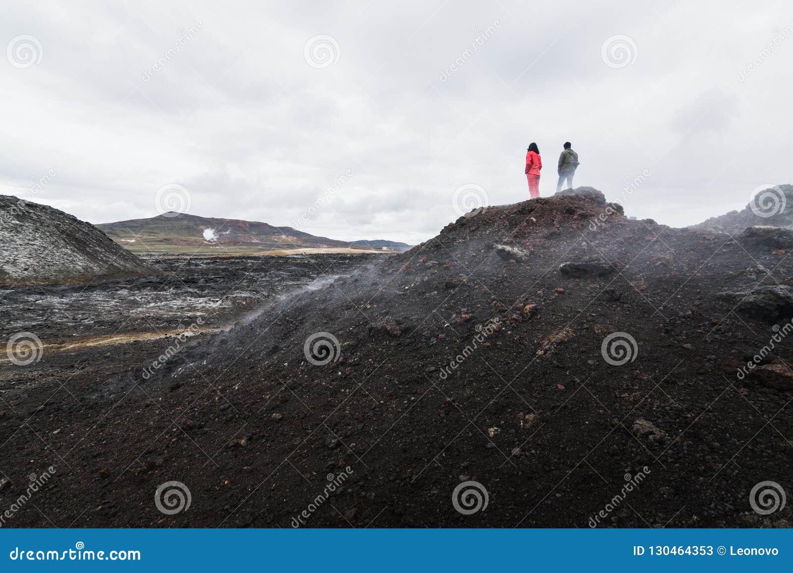 De vrouw en de man stellen status op Krafla-het gebied van de vulkaanlava rond Leirhnjukur-bergpiek voor, IJsland