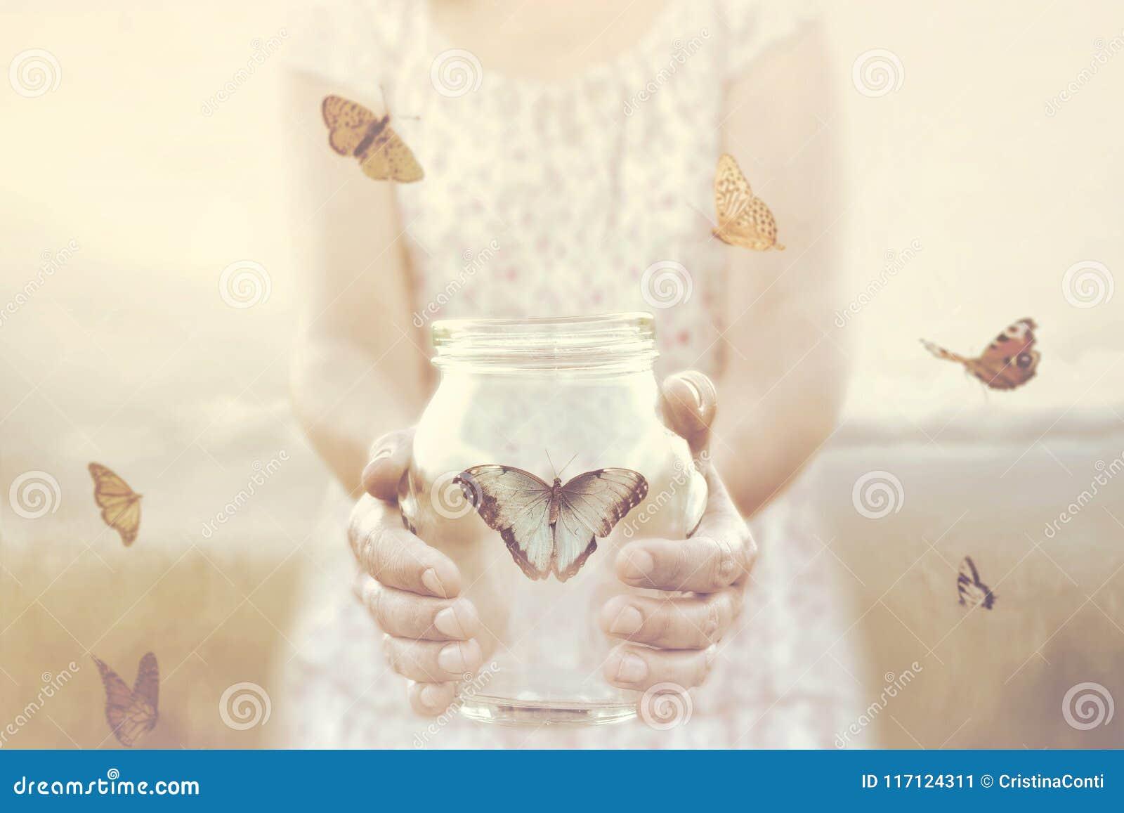 De vrouw geeft vrijheid aan sommige die vlinders in een glasvaas wordt ingesloten