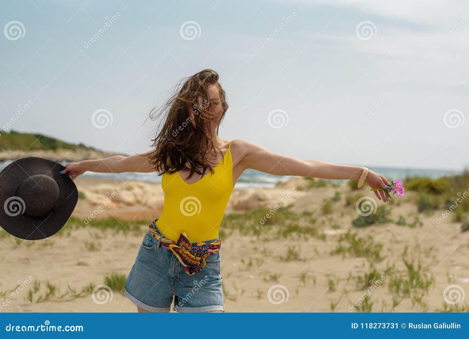 De vrouw geniet van lopend op het zand op de kust