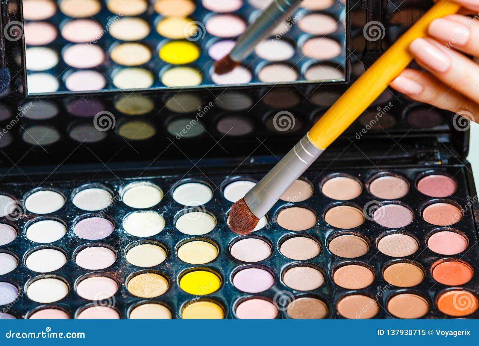 De vrouw houdt het palet en de borstel van make-upoogschaduwwen