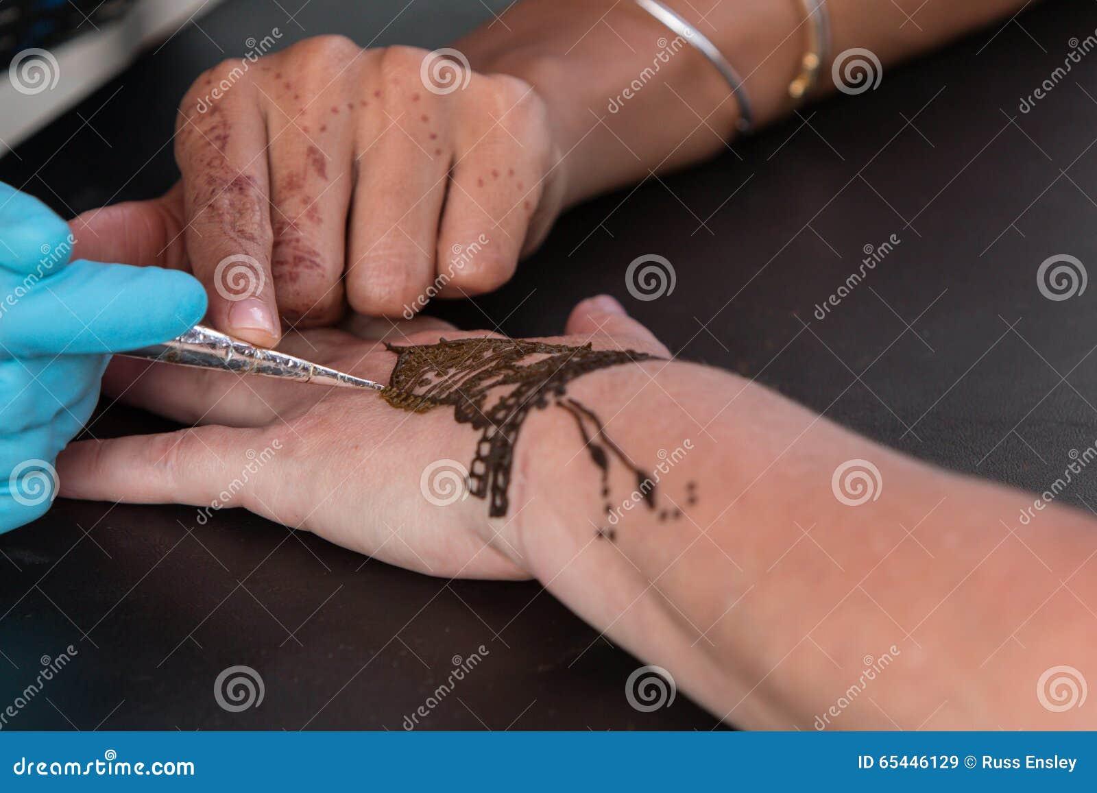 De Vrouw Krijgt Tijdelijke Henna Tattoo On Hand Redactionele