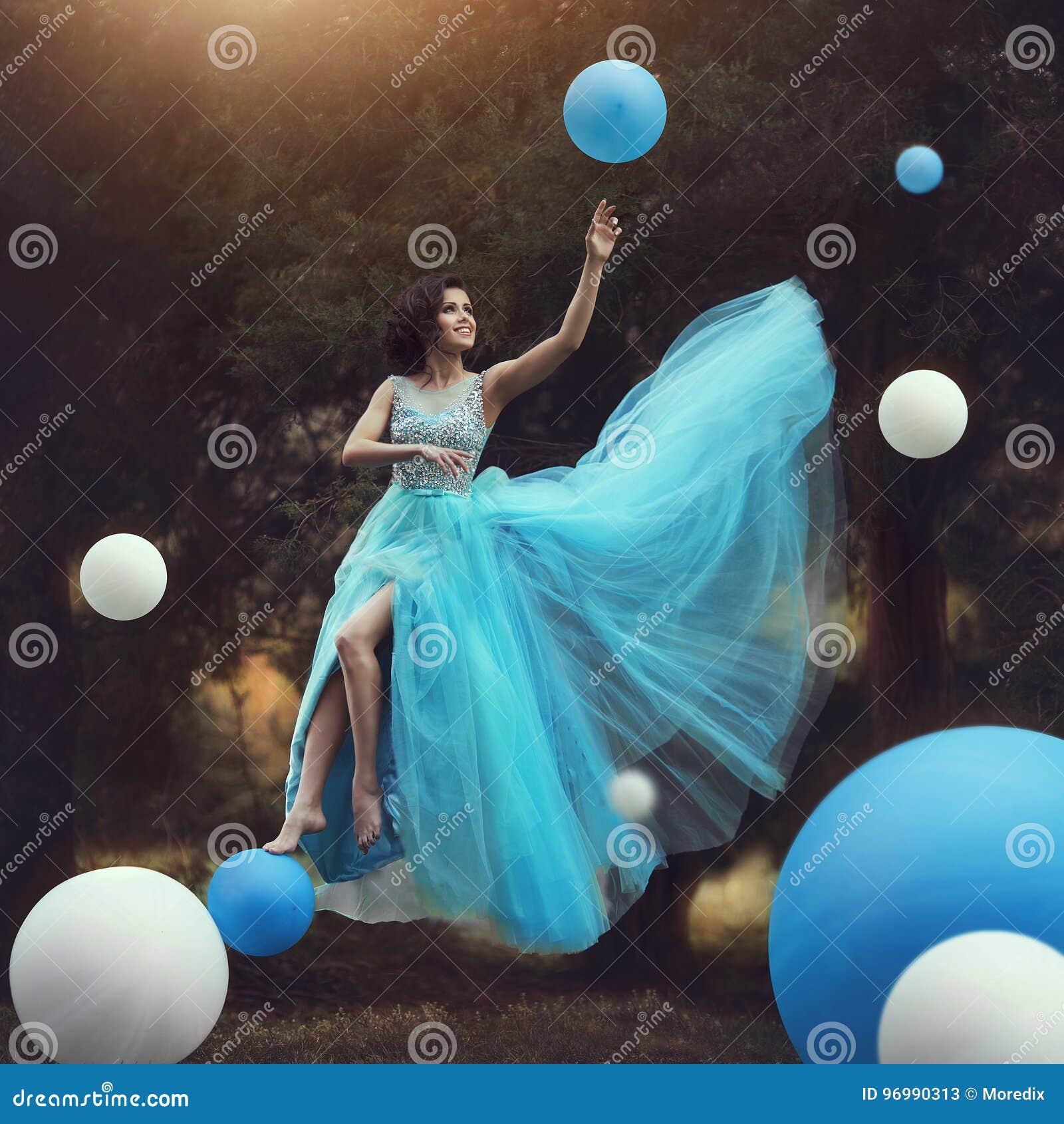 De Vrouw levitatie ondergaat Een mooi meisje in een blauwe pluizige toga Leets samen met ballons Dynamische kunstfotografie fanta