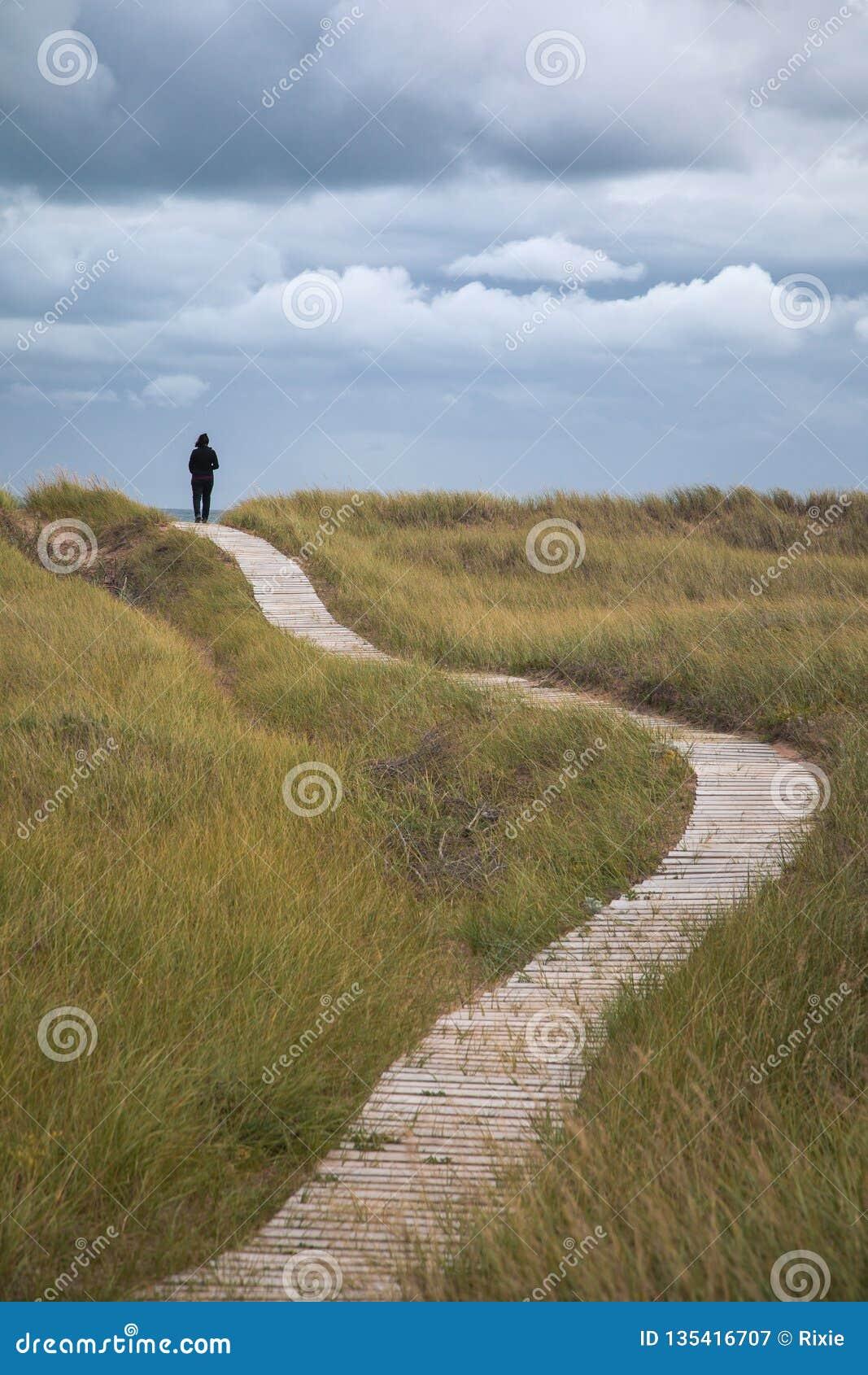 De vrouw loopt de duinen van Iles DE La Madeleine