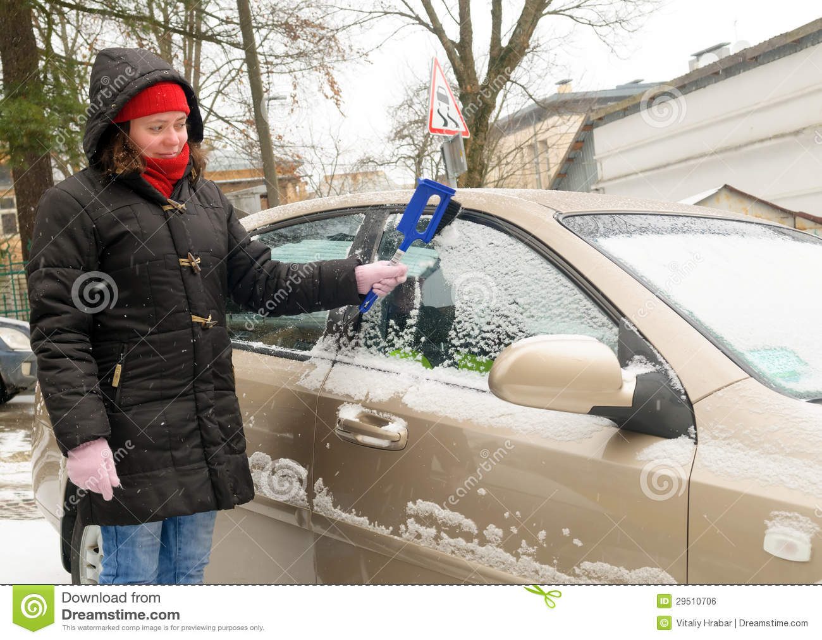 De vrouw maakt het windscherm van de sneeuwauto schoon